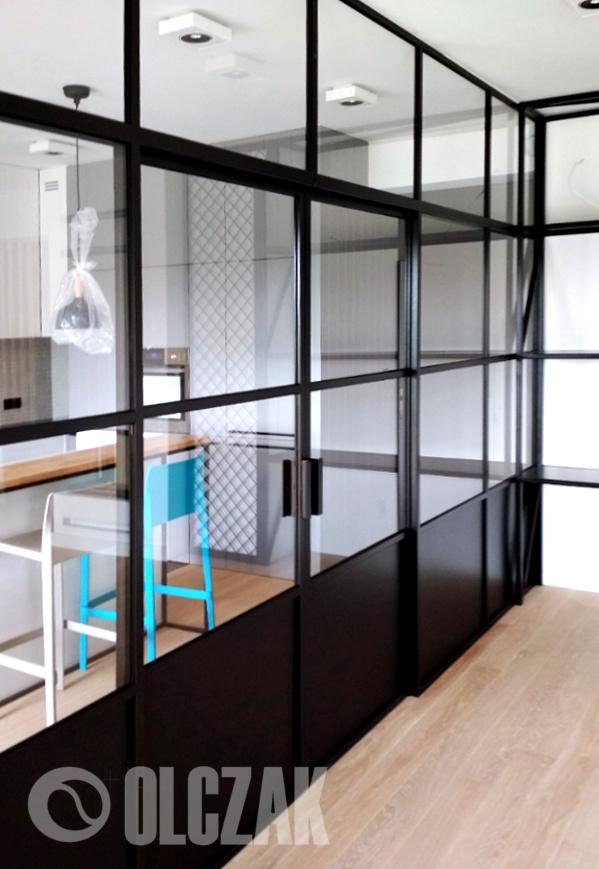 Przeszklenie w stalowej ramie oddziela kuchnię od salonu.